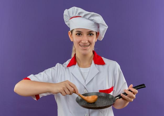 Lächelnder junger hübscher koch in der kochuniform mit zahnspangen, die bratpfanne und löffel lokalisiert auf lila raum halten