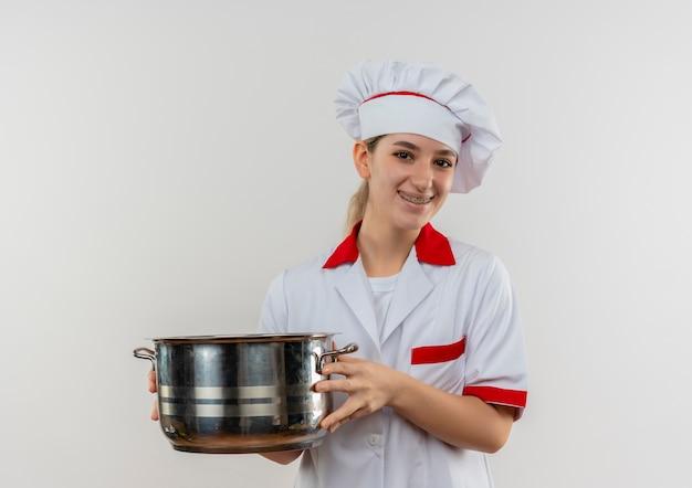 Lächelnder junger hübscher koch in der kochuniform mit zahnspangen, die topf halten lokalisiert auf weißem raum halten