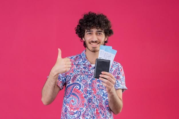 Lächelnder junger hübscher lockiger reisender mann, der brieftasche und flugtickets hält und daumen oben auf isolierter rosa wand mit kopienraum zeigt