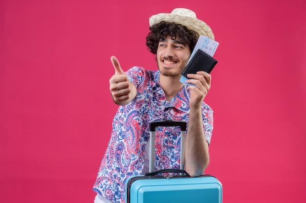 Lächelnder junger hübscher lockiger reisender mann, der hut hält, der brieftasche und flugtickets hält daumen zeigt und arm auf koffer auf isolierte rosa wand mit kopienraum setzt