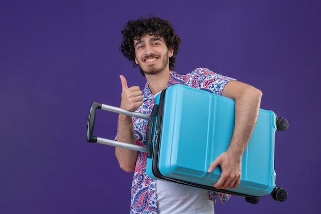Lächelnder junger hübscher lockiger reisender mann, der koffer hält daumen oben auf isolierter lila wand mit kopienraum zeigt