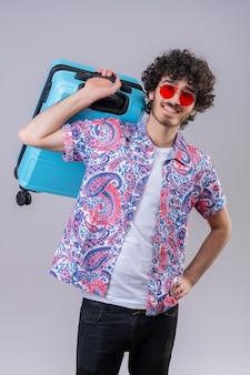 Lächelnder junger hübscher lockiger reisender mann, der sonnenbrille trägt und koffer auf schulter mit hand auf taille auf isolierter weißer wand hält