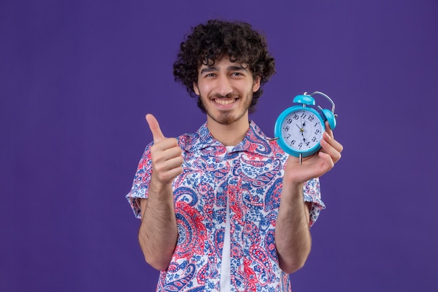 Lächelnder junger hübscher lockiger reisender mann, der wecker hält daumen oben auf isolierter lila wand mit kopienraum zeigt