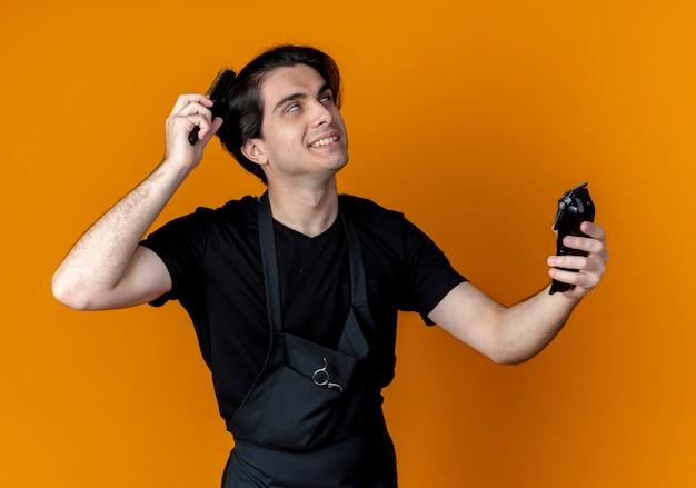 Lächelnder junger hübscher männlicher friseur in der uniform, die haarschneidemaschinen hält und haare isoliert auf orange kämmt