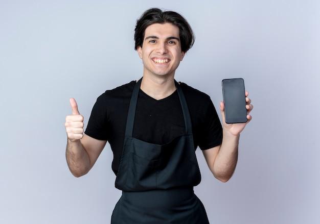 Lächelnder junger hübscher männlicher friseur in der uniform, die telefon seinen daumen oben auf weißer wand hält