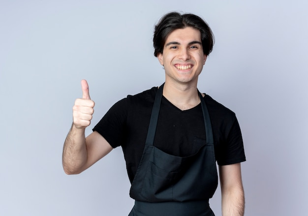 Lächelnder junger hübscher männlicher friseur in uniform sein daumen oben auf weiß isoliert