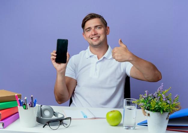 Lächelnder junger hübscher männlicher student, der am schreibtisch mit schulwerkzeugen sitzt, hält telefon seinen daumen oben isoliert auf blau