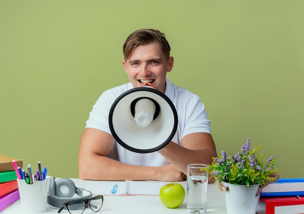 Lächelnder junger hübscher männlicher student, der mit schulwerkzeugen am schreibtisch sitzt, spricht auf lautsprecher, der auf olivgrün isoliert wird