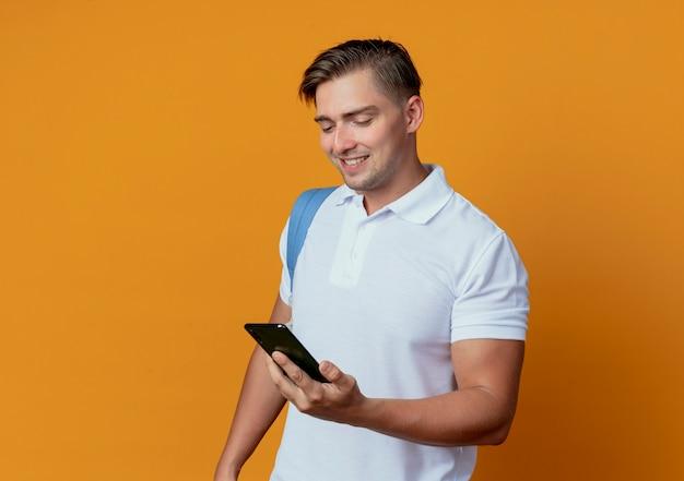 Lächelnder junger hübscher männlicher student, der rückentasche hält und telefon lokalisiert auf orange hält