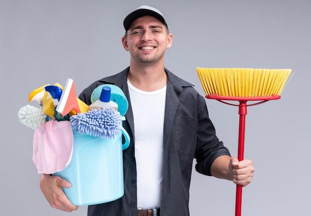 Lächelnder junger hübscher reinigungsmann, der t-shirt und kappe hält, die eimer mit reinigungswerkzeugen mit mopp lokalisiert auf weißer wand hält