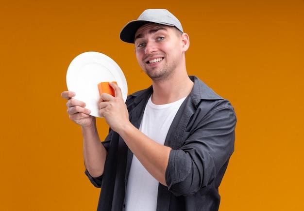 Lächelnder junger hübscher reinigungsmann, der t-shirt und kappe hält platte und schwamm lokalisiert auf orange wand trägt