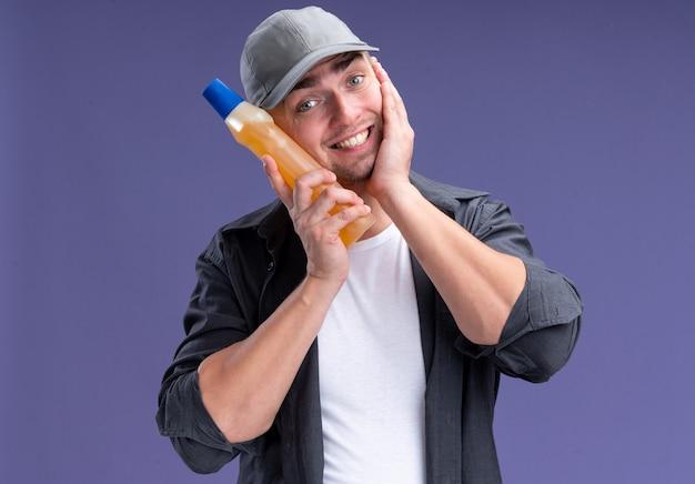 Lächelnder junger hübscher reinigungsmann, der t-shirt und kappe hält reinigungsmittel auf wange lokalisiert auf lila wand trägt