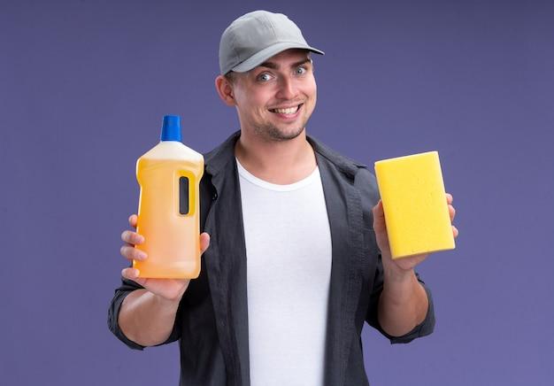 Lächelnder junger hübscher reinigungsmann, der t-shirt und kappe hält reinigungsmittel mit schwamm lokalisiert auf lila wand trägt