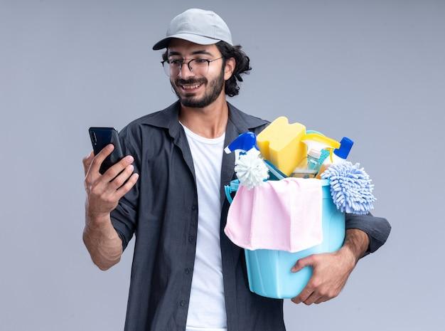 Lächelnder junger hübscher reinigungsmann, der t-shirt und kappe trägt, eimer mit reinigungswerkzeugen hält und telefon in seiner hand lokalisiert auf weißer wand betrachtet