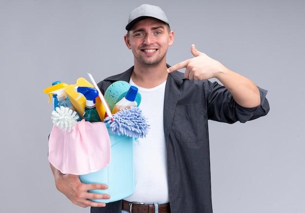 Lächelnder junger hübscher reinigungsmann, der t-shirt und kappenhaltung trägt und auf eimer mit reinigungswerkzeugen zeigt, die auf weißer wand lokalisiert werden