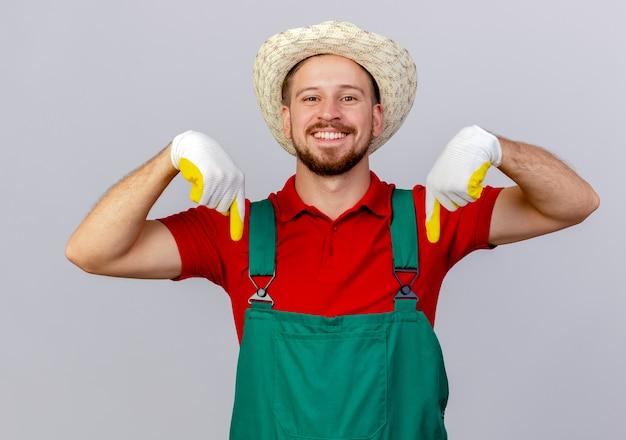 Lächelnder junger hübscher slawischer gärtner in der uniform, die gartenhandschuhe und hut trägt, die lokal auf weiße wand zeigen
