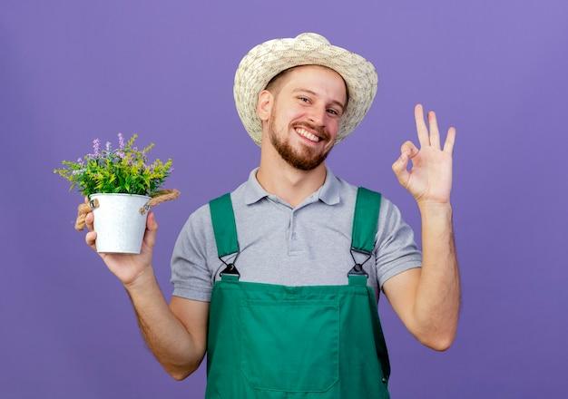 Lächelnder junger hübscher slawischer gärtner in der uniform und im hut, der blumentopf hält, der ok zeichen lokalisiert auf lila wand hält