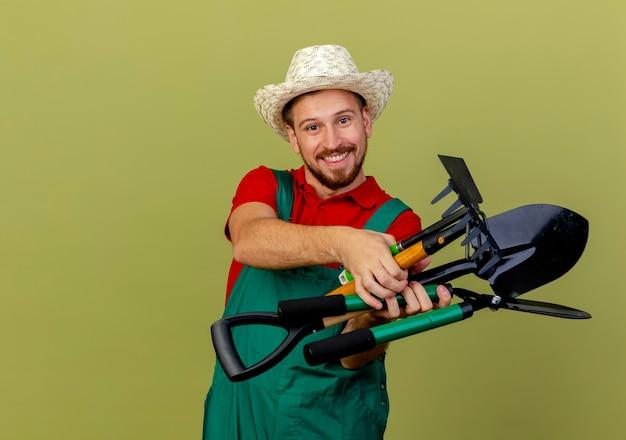 Lächelnder junger hübscher slawischer gärtner in der uniform und im hut, die gärtnerwerkzeuge halten, die lokal suchen