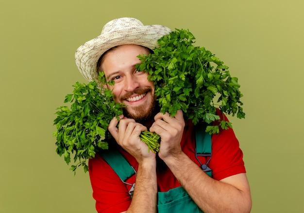 Lächelnder junger hübscher slawischer gärtner in der uniform und im hut, die koriander nahe gesicht lokalisiert auf olivgrüner wand halten