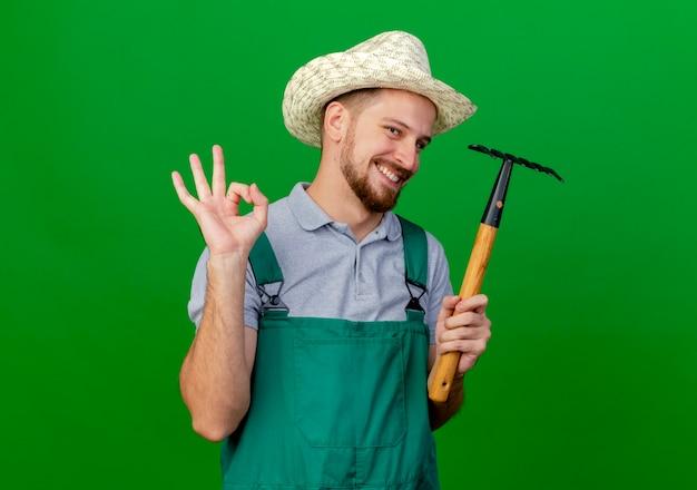 Lächelnder junger hübscher slawischer gärtner in uniform und hut, der rechen hält, der ok zeichen lokalisiert auf grüner wand mit kopienraum sucht
