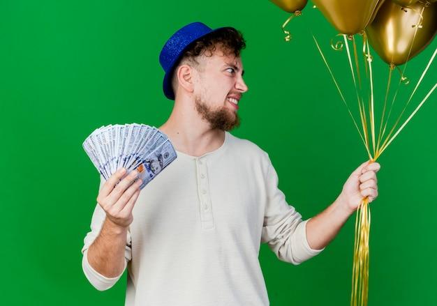 Lächelnder junger hübscher slawischer partei-kerl, der parteihut hält, der ballons und geld hält, die seite lokalisiert auf grünem hintergrund betrachten