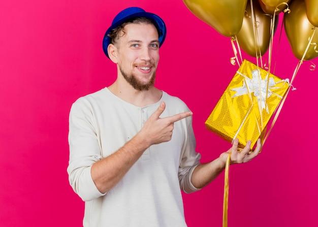 Lächelnder junger hübscher slawischer partei-kerl, der parteihut hält, der luftballons und geschenkbox hält, die nach vorne zeigt auf geschenkbox und luftballons lokalisiert auf rosa wand mit kopienraum
