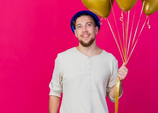 Lächelnder junger hübscher slawischer party-typ, der partyhut hält, der ballons hält, die front lokal auf rosa wand mit kopienraum betrachten