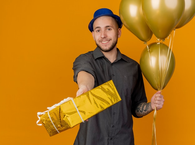 Lächelnder junger hübscher slawischer party-typ, der partyhut hält, der ballons hält, die geschenkverpackung in richtung kamera lokalisiert auf orange hintergrund strecken