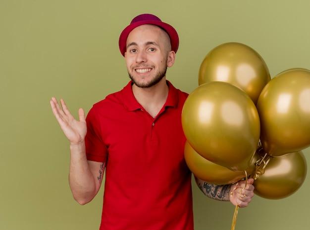 Lächelnder junger hübscher slawischer party-typ, der partyhut hält, der ballons hält, die kamera zeigt, die leere hand lokalisiert auf olivgrünem hintergrund zeigt