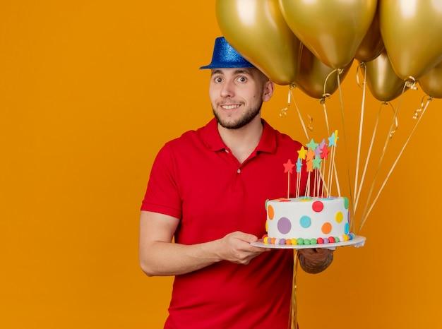 Lächelnder junger hübscher slawischer party-typ, der partyhut hält, der ballons und geburtstagstorte hält und kamera lokalisiert auf orange hintergrund mit kopienraum betrachtet