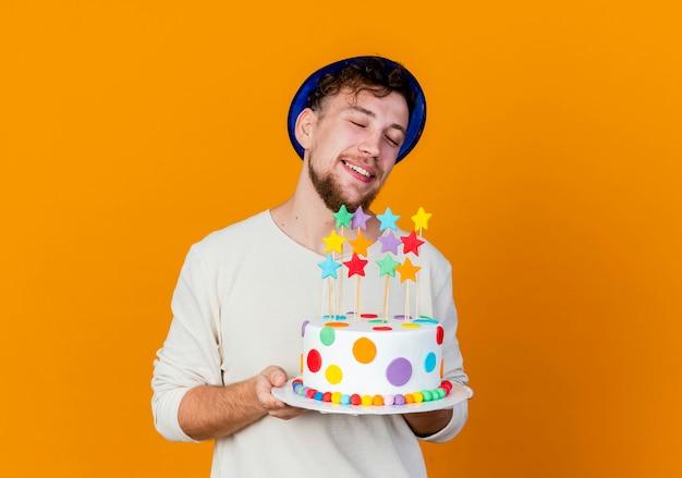 Lächelnder junger hübscher slawischer party-typ, der partyhut hält, der geburtstagstorte mit sternen lokalisiert auf orange hintergrund mit kopienraum hält