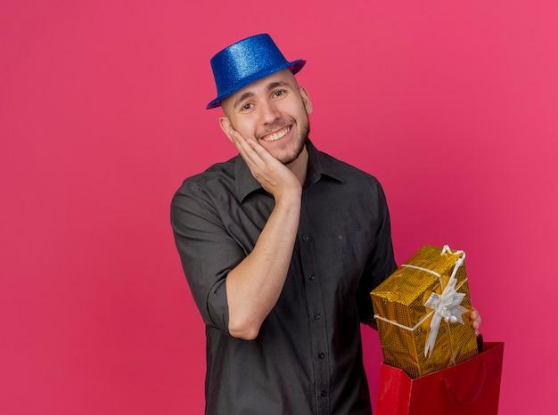 Lächelnder junger hübscher slawischer party-typ, der partyhut hält, der geschenkpackung mit papiertüte betrachtet kamera betrachtet, die hand auf gesicht lokalisiert auf purpurrotem hintergrund mit kopienraum setzt