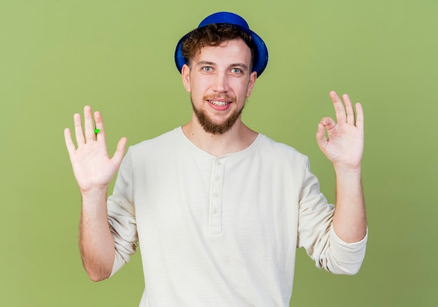 Lächelnder junger hübscher slawischer party-typ, der partyhut hält, der partygebläse hält, das kamera betrachtet, das ok zeichen lokalisiert auf olivgrünem hintergrund tut