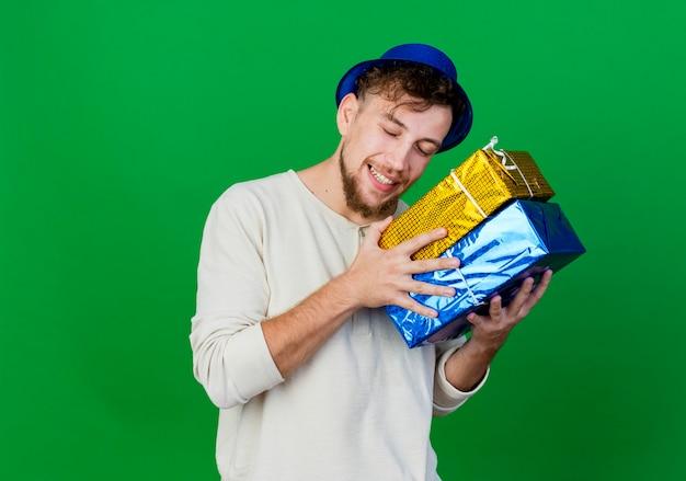 Lächelnder junger hübscher slawischer party-typ, der partyhut trägt, der geschenkboxen nahe kopf mit geschlossenen augen lokalisiert auf grünem hintergrund mit kopienraum hält