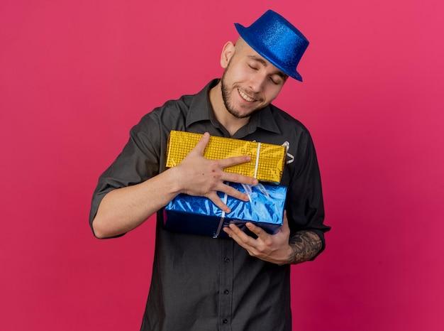 Lächelnder junger hübscher slawischer party-typ, der partyhut trägt, der geschenkverpackungen mit geschlossenen augen hält, lokalisiert auf purpurrotem hintergrund mit kopienraum
