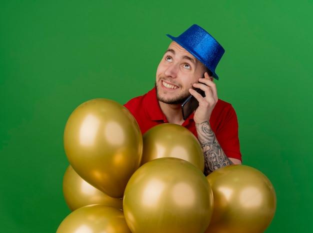 Lächelnder junger hübscher slawischer party-typ, der partyhut trägt, der hinter luftballons steht, die oben auf telefon lokalisiert auf grünem hintergrund suchen