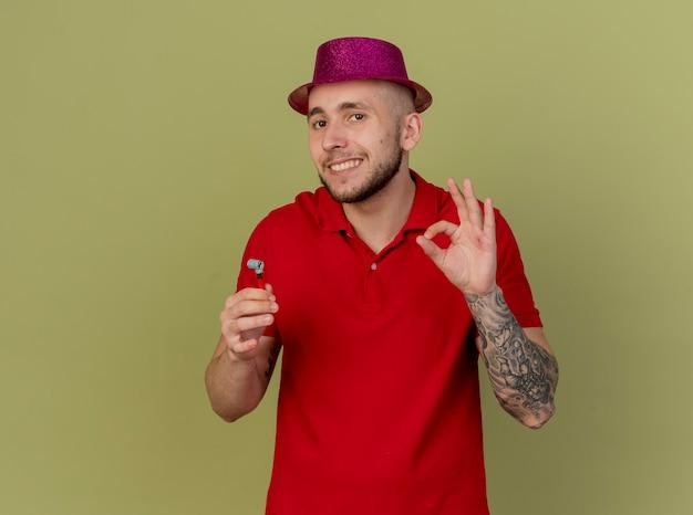 Lächelnder junger hübscher slawischer party-typ, der partyhut trägt, der kamera hält party-gebläse tut ok zeichen lokalisiert auf olivgrünem hintergrund mit kopienraum