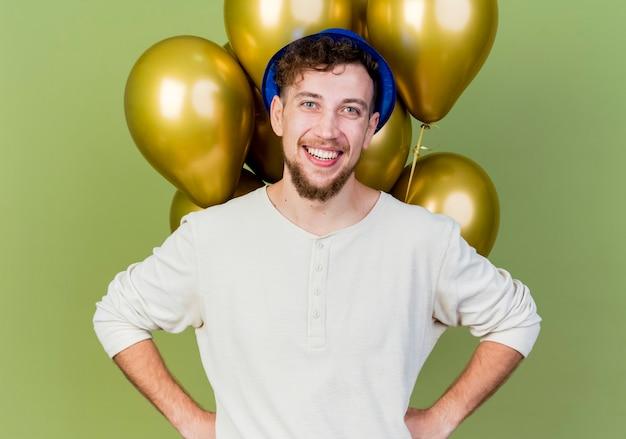 Lächelnder junger hübscher slawischer party-typ, der partyhut trägt, der vor ballons steht und kamera betrachtet, die hände auf taille lokalisiert auf olivgrünem hintergrund hält