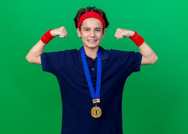 Lächelnder junger hübscher sportlicher junge, der stirnband und armbänder und medaille um hals mit zahnspangen trägt, die nach vorne schauen, starke geste lokalisiert auf grüner wand