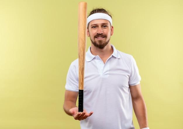 Lächelnder junger hübscher sportlicher mann, der stirnband und armbänder hält baseballschläger lokalisiert auf grünfläche trägt