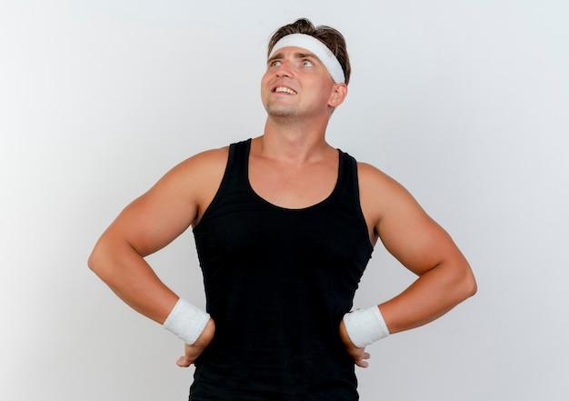 Lächelnder junger hübscher sportlicher mann, der stirnband und armbänder trägt, die mit händen auf taille lokalisiert auf weißer wand suchen