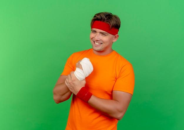 Lächelnder junger hübscher sportlicher mann, der stirnband und armbänder trägt, die sein verletztes handgelenk halten, das mit verband eingewickelt wird, der auf grüner wand lokalisiert wird