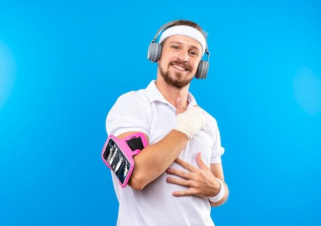 Lächelnder junger hübscher sportlicher mann, der stirnband und armbänder und kopfhörer mit telefonarmband trägt, die hände auf bauch und brust mit verletztem handgelenk setzen, das mit verband umwickelt wird, der auf blauem raum isoliert wird