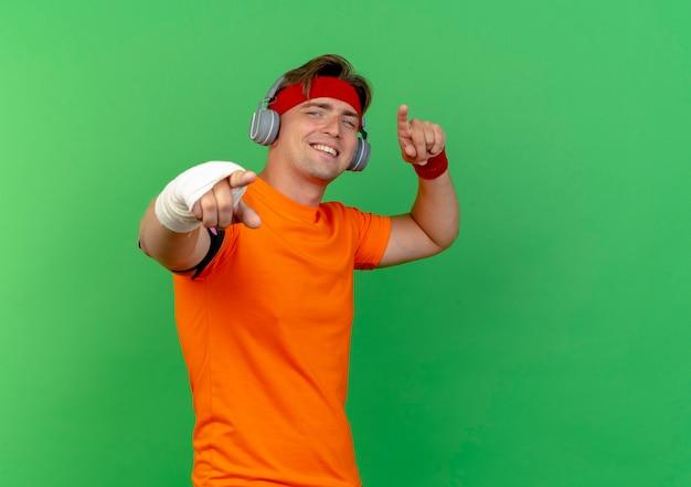 Lächelnder junger hübscher sportlicher mann, der stirnband und armbänder und kopfhörer mit verletztem handgelenk trägt, das mit verband umwickelt wird, der sie geste an der front lokalisiert auf grüner wand tut