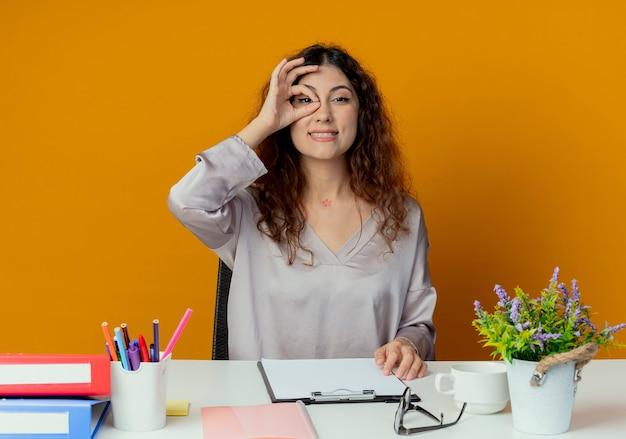 Lächelnder junger hübscher weiblicher büroangestellter, der am schreibtisch mit bürowerkzeugen sitzt, die blickgeste lokalisiert auf orange zeigen
