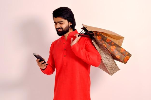 Lächelnder junger indischer mann, der kurta hält, die einkaufstaschen hält und handy betrachtet