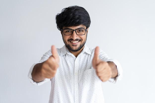 Lächelnder junger indischer mann, der sich daumen zeigt und kamera betrachtet.