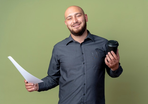 Lächelnder junger kahler callcenter-mann, der dokument und plastikkaffeetasse lokalisiert auf olivgrüner wand hält