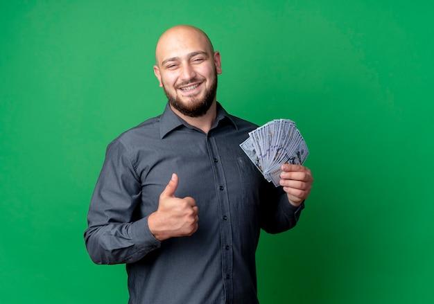Lächelnder junger kahler callcenter-mann, der geld hält und daumen oben auf grüner wand zeigt