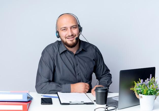 Lächelnder junger kahler callcenter-mann, der headset am schreibtisch mit arbeitswerkzeugen sitzt, die hände auf schreibtisch lokalisiert auf weißer wand setzen